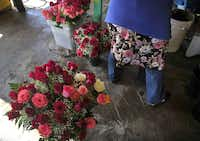 Gloria Jaimes appropriately wears a flower dress for the day as she works to arrange displays at her daughter's flower shop, Mariola's Flowers, in the Farmers Market district.