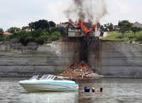 Boaters watched as the home  overlooking Lake Whitney was engulfed by fire Friday.( Rod Aydelotte  - Herald )