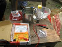 Pulak's home-based rapid arsenic water test, shown here in a Bangladesh village, includes a multimeter, test paper made out of tissue and business cards and nano magnet.(Photo submitted by THABIT PULAK)