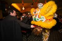 State Rep. Matt Rinaldi fed the lion a red envelope with money for good luck at OCA's Lunar New Year Banquet at Maxim's in Richardson.( Jarvis Jacobs )