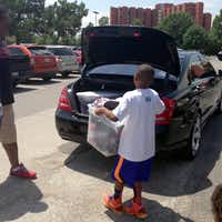 Rowlett resident Jay Fair loads 82 pairs of shoes into his family's car. Fair collected the shoes this summer to give to victims of the Moore, Okla. tornado for his birthday in lieu of gifts.(Christina Fair - Submitted photo)