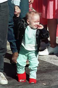 19-month-old Jessica McClure holds her mother's hand as they leave the Midland Memorial Hospital on Nov. 20, 1987. The toddler spent more than a month in the hospital after she was rescued from the abandoned water well.