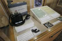 A Motorola motorcycle police radio transmitter, with a speaker and microphone, is on display with documents related to the JFK motorcade in an exhibit at Dallas City Hall. The transmitter was mounted to one of the Dallas police motorcycles used in the presidential motorcade.