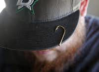 Brian Clark sports a fishhook on the brim of his cap. Clark bought Fisherman's Supply near Lake Ray Hubbard last year and renamed it Clark's Tackle Box.( Guy Reynolds  -  Staff Photographer )