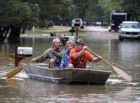 J.B. Neckar (right) and his brother Johnny paddled their mother away from her flooded home near Downsville on Saturday. Rains have forced parts of the Brazos River out of its banks, endangering Gelene Neckar and others in the small community outside of Waco.(Jerry Larson -  Waco Tribune Herald )