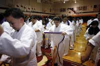 Maria Santos, 12, (center) and other students put on their new belts during a Kickstart Kids karate belt ceremony at Austin Middle School in Irving. A protest led the district to keep the program even as it decided to cut 149 teachers.