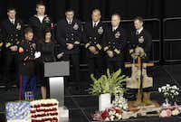 Taya Kyle is consoled by a member of the military as she gets emotional while speaking about her husband Chris Kyle during a memorial service for Chris Kyle at Cowboys Stadium in Arlington on February 11, 2013.