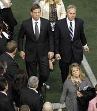 Former Dallas Cowboys quarterback Troy Aikman (left) and Dallas Cowboys director of public relations Rich Dalrymple exit the field after a memorial service for Chris Kyle at Cowboys Stadium in Arlington on February 11, 2013.