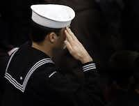 A sailor salutes during the memorial service for former Navy SEAL Chris Kyle on Monday, February 11, 2013 at Cowboys Stadium in Arlington, Texas.