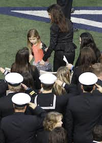 Taya Kyle, wife of former Navy SEAL Chris Kyle, helps her daughter to her seat at the beginning of her husband's Memorial Service on Monday, February 11, 2013 at Cowboys Stadium in Arlington, Texas.