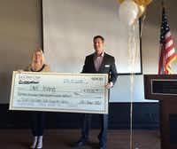 Joy Goodrum, left, of the Irving Chamber, accepts a check from Mike Goff on behalf of La Cima Club for One Irving.Courtesy