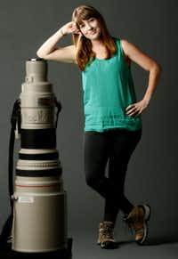 Rose Baca poses with a Canon 600mm lens. Good to note: the size of the lens is clearly a photo illusion as it is not almost as tall as Rose. (Nathan Hunsinger/The Dallas Morning News)