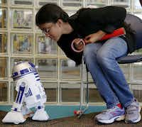 Sahib Kaur, 10, of Plano, Texas, gazes at an R2-D2 self-animated toy while she makes a light saber during the Library Geek-a-Thon at Haggard Library in Plano, Texas Thursday August 6, 2015. Children dressed as different characters, played video games, created light sabers, picked from free comics and participated in a photo shoot. (Andy Jacobsohn/The Dallas Morning News)