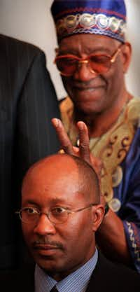 Dallas City Councilman Al Lipscomb (rear) puts 'rabbit ears' on Dallas Mayor Ron Kirk during a council photo session in January 2000.
