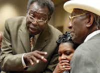 Dallas City Council member James L. Fantroy (left) talks to Al Lipscomb (right) and an unidentified woman during an August 2003 council meeting.