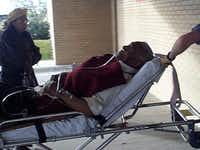 Al Lipscomb is wheeled into an Amarillo hospital in January 2000 as his wife, Lovie, watches. Lipscomb was hospitalized after complaining of shortness of breath shortly before closing arguments in his federal bribery trial.