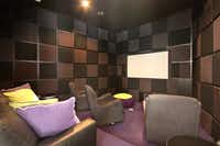 Plush chairs and padded walls are features in the home's theater room.(Dave Perry-Miller & Associates)