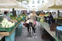 A customer pays a stallholder for a bag of produce while sitting on her bicycle at an open market in Ljubljana, Slovenia.
