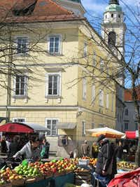 Steps from St. Nicholas Cathedral, a customer shops for apples in Ljubljana's Central Market.