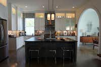 A six-burner range adds a note of color to the kitchen. Polished concrete floors gleam throughout the first floor..