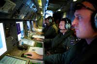 Crew members of a Royal New Zealand Air Force P-3 Orion operate radar and sensor systems while taking part in the search for Malaysia Airlines Flight MH370.Richard Wainwright  - Presse