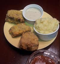 Southern Style Chicken-Fried Meatloaf is served with garlic mashed potatoes, cream gravy and a catsup-brown sugar glaze for dipping.