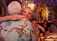 Pam Wood and Tracy Cross hug as they and other members of a Parkinson's disease online support group meet in person for the first time at Buca di Beppo restaurant in Dallas.