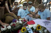 Israeli mourners gathered Monday at the grave of Capt. Liad Lavi, who died of wounds from the Gaza fighting, during his funeral in the southern Israeli village of Meitar.( Ariel Schalit  -  The Associated Press )