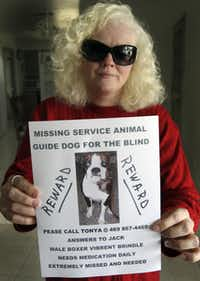 Tonya Gaskill poses with a poster for her lost dog at her home in Carrollton.