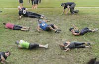 Participants in he Original Mud Run roll down a hill into a smelly muck during.
