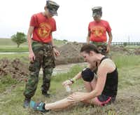 Stephanie Greenhaw, cleans a wound she suffered while competing in the Original Mud Run in Fort Worth on April 14, 2012.
