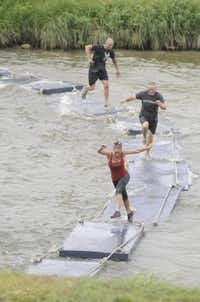 Participants in the Original Mud Run cross the Trinity River on floating pads during the event in Fort Worth on April 14, 2012.