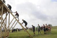 Participants in the Original Mud Run climb up the back end of a slide.