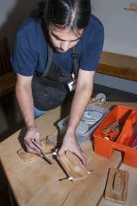 An Explora staff member shows how to build a table-top sailing craft, which will be propelled by a fan.  Other hands-on exhibits include a water flow table, whirlpool vortex and a bank of Bernoulli blowers.