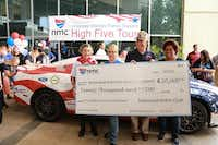 Hughlene Stokes (from left), Heidi Vincent, Col. John Folsom and Donna Smith receives a check at the High Five Tour stop at National Motor Club in Irving.( Photo submitted by NATIONAL MOTOR CLUB )