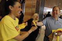 Dickey's Barbecue Pit employees Jasmine Elias (left) and Kate Morganelli handed out T-shirts and other promotional materials to prospective customers such as Peter Sagior on Wednesday at Love Field.