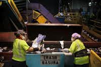 Marisol Portillo (left) and Maria Mendoza separate trash from recyclables at a Community Waste Disposal facility in Dallas.