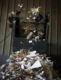 Trash flies off a conveyor belt at a Community Waste Disposal material recycling facility in Dallas.
