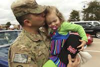 U.S. Army Capt. Tim Nelson kisses 3-year-old Elise Nelson at the parade.