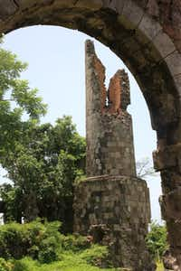 The ruins of an old smoke stack from an 1800s sugar cane plantation still stand on the 100 acre land that is now the Golden Rock Inn Nevis property owned by American artists Helen and Brice Marden.