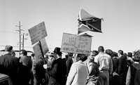 In this Nov. 22, 1963 file photo, people, including right-wing protesters carrying a Confederate flag and anti-Kennedy placards, await the arrival of President John F. Kennedy at Love Field in Dallas. The 50th anniversary of Kennedy's assassination throws a new spotlight on the deep hostility toward Kennedy that some Dallasites voiced before the assassination. (AP Photo)