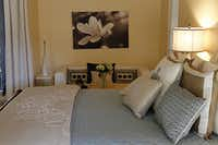 """Soft green replaced """"bordello red"""" on the walls of the master bedroom."""