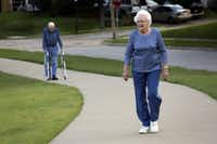Charlotte Davis, 85, who has osteoporosis, walks near her Farmers Branch home. In the background is her husband Hollis, who is nearby with her walker in case she encounters uneven ground.