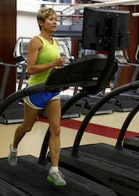 Gina Garcia, the assistant fitness director at SMU, starts her work out with a 15 minute warm up on the treadmill at SMU's Dedman Center.(Ron Heflin)