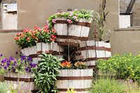 Stacked whiskey barrels overflow with flowers in front of the Feed and Seed Barn.Feed and Seed Barn