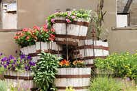 Stacked whiskey barrels overflow with flowers in front of the Feed and Seed Barn.( Feed and Seed Barn )