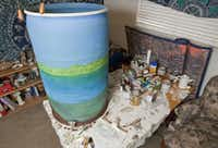 Homeowner Georgia Rayna paints designs on her plastic rain barrels to mask their jarring color.