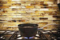 The tiles on the backsplash of this kitchen are made from recycled glass.   The Lakewood house was built by Greenbrook Homes, which specializes in green-friendly construction and design.