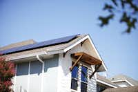 Rooftop solar panels offset energy consumption. Overhangs above windows deflect the sun's rays.