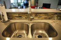The kitchen's backsplash tile from Walker Zanger is made of recycled glass. Kitchen countertops are CaesarStone quartz.